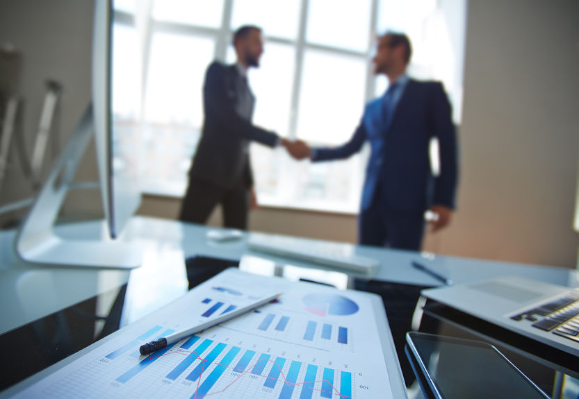 44276751 - business document at workplace with business partners handshaking on background